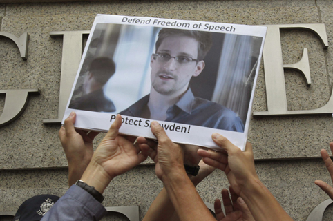 File photo of protesters holding photo of Snowden during a demonstration outside the U.S. Consulate in Hong Kong